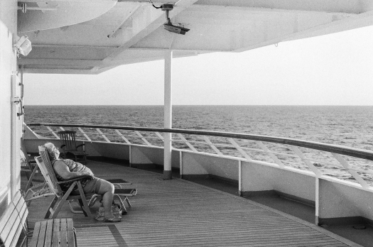 A passenger soaks up the last bit of sun of the day at the aft of the ship